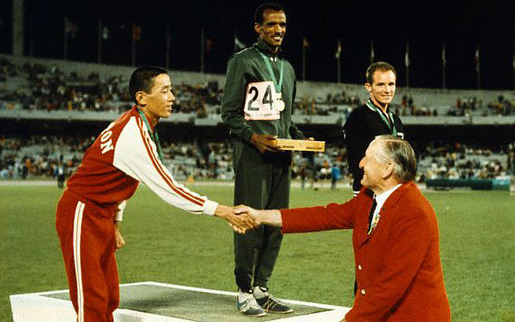 20 Oct 1968, Mexico City, Mexico --- Original caption: Winners of the Marathon run with their medals. From left, second place winner Kenji Kimihara of Japan, shaking hands with official; Mamo Wolde of Ethiopia (first place) and Michael Ryan of New Zealand, who won the Bronze medal for third place in th 1968 Olympics. --- Image by © Bettmann/CORBIS